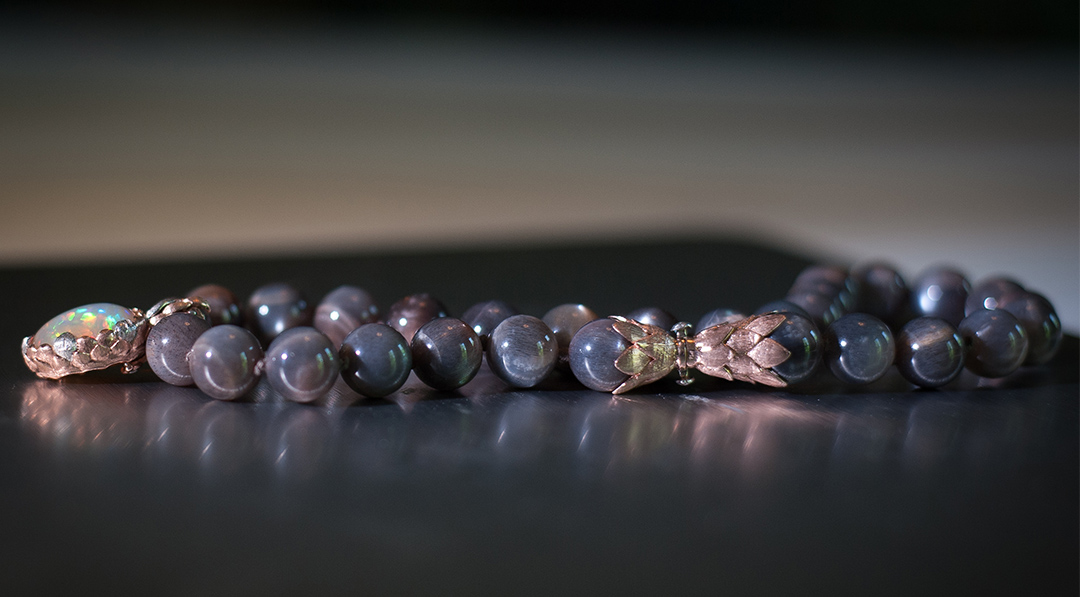 """Cynthia Renee full custom design necklace in 14-karat rose-gold and platinum featuring 12.80 carat Mexican """"Contra Luz"""" opal and 12-mm grey moonstone beads. Photo by Christine Prisk."""