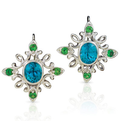 "Calligraphy"" earrings in 18 karat white gold featuring 12.20 ct. pair of vivid Blue Zircon accented by 1.43 cts. of Tsavorite garnets; ""swan-neck"" wire with locking back."