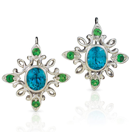 """Calligraphy"""" earrings in 18 karat white gold featuring 12.20 ct. pair of vivid Blue Zircon accented by 1.43 cts. of Tsavorite garnets; """"swan-neck"""" wire with locking back."""