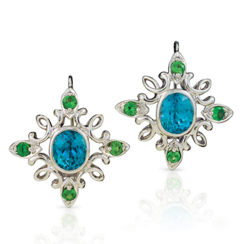 """Calligraphy"""" earrings in 18 karat white gold featuring 12.20 ct. pair of vivid Blue Zircon accented by 1.43 cts. of Tsavorite garnets; """"swan-neck"""" wire with locking back. Calligraphy"""" earrings in 18 karat white gold featuring 12.20 ct. pair of vivid Blue Zircon accented by 1.43 cts. of Tsavorite garnets; """"swan-neck"""" wire with locking back. Calligraphy"""" earrings in 18 karat white gold featuring 12.20 carats pair of vivid Blue Zircon accented by 1.43 carats of Tsavorite garnets."""