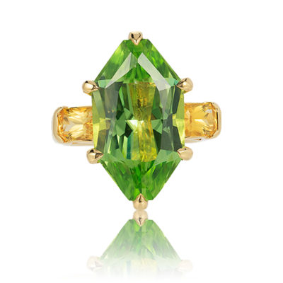 Three-stone ring in 18 kt yg featuring 10.86 ct. designer-cut Peridot accented by 1.29 ct. pair of Yellow Sapphire; size 7, but can size to fit.