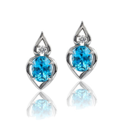 """Pantea"" earrings in palladium featuring 5.87 ct. pair vivid Blue Zircon accented by 0.15 cts. fine round diamond; post with friction back. Tail on back support drop."