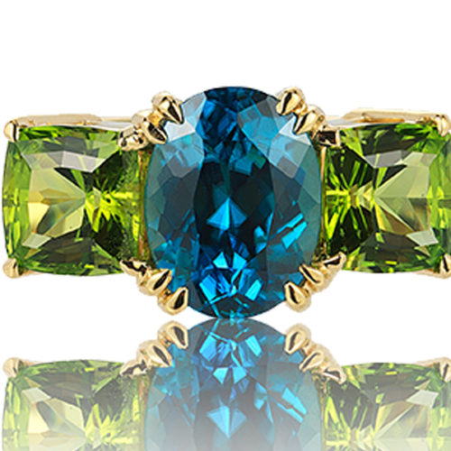 """""""Heaven & Earth"""" three-stone ring in 18 karat yellow gold featuring a 5.49 carats vivid Blue Zircon combined with a 4.22 carats pair of Peridot."""