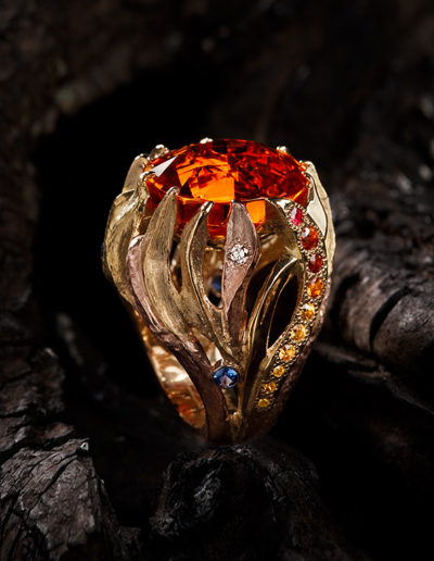 """Ring of Fire"" ~ Cynthia Renée full custom design ring in 18 karat yellow gold, 14 karat rose gold and platinum featuring 22 carat hot orange spessartite garnet (Namibia-natural color) accented with yellow diamond, yellow sapphire, spessartite garnet and red spinel and blue sapphire; winner of Custom Design Distinction Award from the Manufacturing Jewelers and Silversmiths Association.  Photo by Jan Balster."