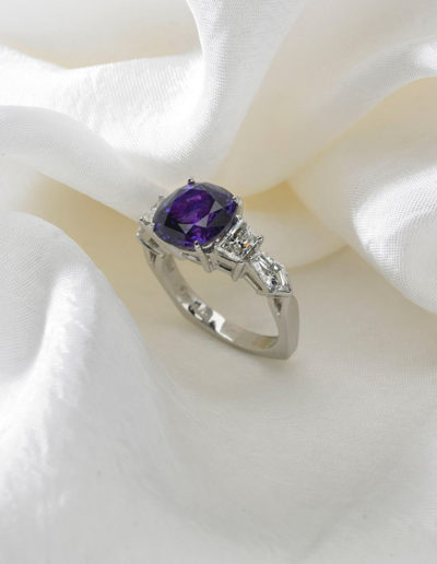 "Cynthia Renée ""Purple Moon"" ring featuring 7.35 carat Purple Sapphire (Sri Lanka) accented by trapezoid and bullet-shaped diamond pairs and set in 19 karat white gold."