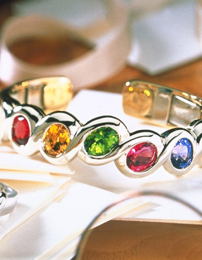 """Grace"" ~ Cynthia Renée cuff bracelet wrapping a collection of oval colored gems with a white gold ribbon. Gems include Red Spinel (Burma), Yellow Sapphire (Sri Lanka), Peridot (China), Red Tourmaline (Nigeria), Tanzanite, Topaz (Brazil), set in 18 karat white gold."