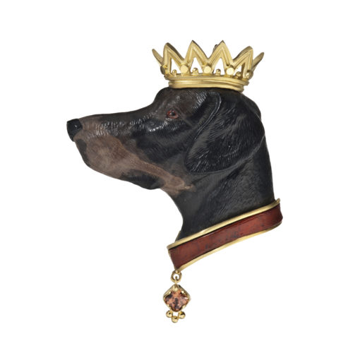 """The """"Faithful Companion"""" brooch/pendant features a hound head hand-carved from petrified wood, with a carnelian collar accented by a 0.50 carat radiant-cut Bronze Zircon dog tag; all set in 18 karat yellow gold."""