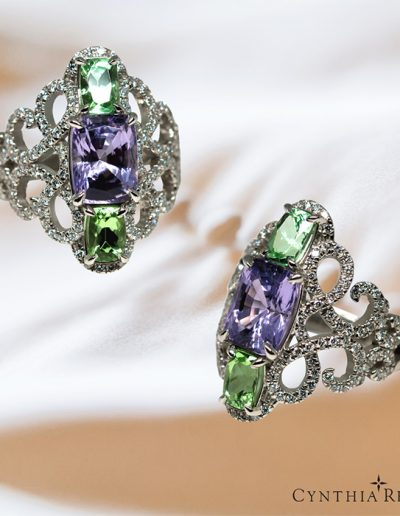 Custom-made three-stone platinum ring featuring a center 3.08 carat lavender spinel and a pair of 1.47 carat minty green garnets, accented by 134 round diamonds totaling 0.76 carats.