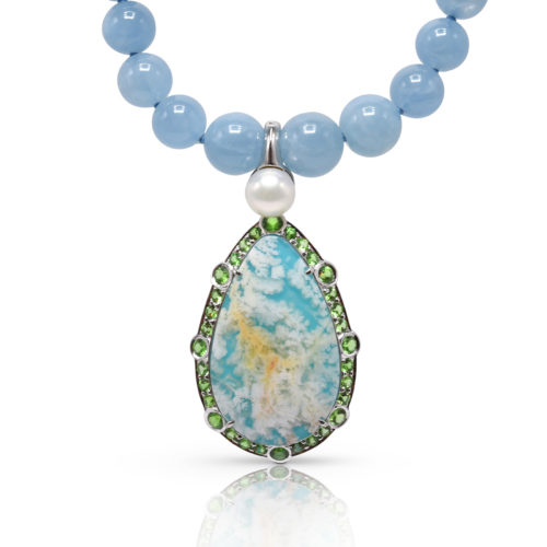 """One-of-a-kind pendant crafted in 18 karat yellow gold featuring a 22.96 carat, pear-shaped """"Coral Sea Turquoise"""" haloed by 3.66 carats of Tsavorite Garnet. Pendant bale is clip-on style for wear over a varity of cords, beads, pearls and chains."""