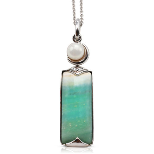 Crescent pendant in 18 karat white gold featuring 8.69 carats natural Opalized Wood and 7-7.5 mm Freshwater Pearl; the opalized wood is found in the West Java Province of Indonesia.