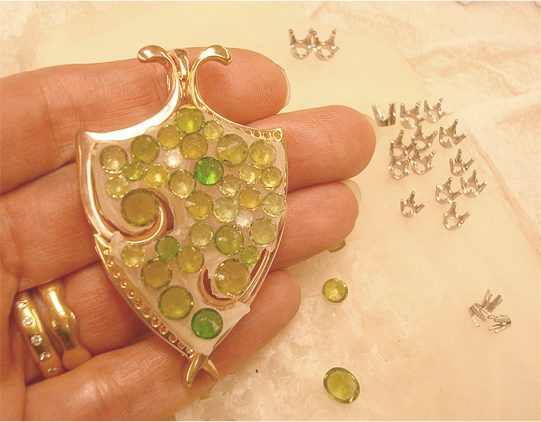 The assembled pendant frame with the demantoid garnets (bottom up) on wax as they would be arranged within the frame.