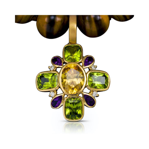 Cynthia Renee's pendant featuring a golden center of Zircon (5.37 carats from Sri Lanka), surrounded by four Peridot (7.17 carats, Pakistan), four Amethyst (0.93 carats from Brazil) and four diamonds (0.12 carats) all set in 18 karat yellow gold.